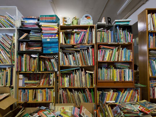Boxes and shelves overflowing with donated books at