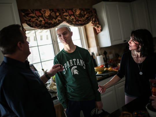 Sam Kell, 16, of Rochester, center, listens to his