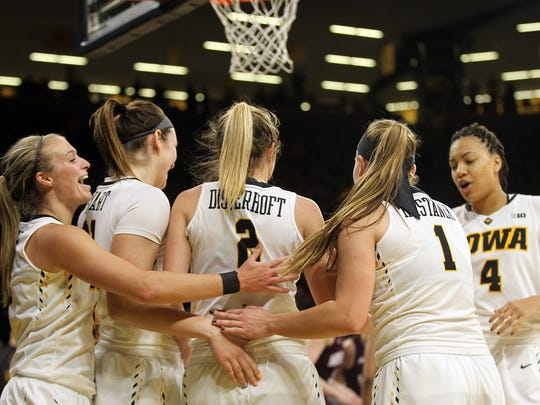 Iowa's Ally Disterhoft gets a group hug after breaking