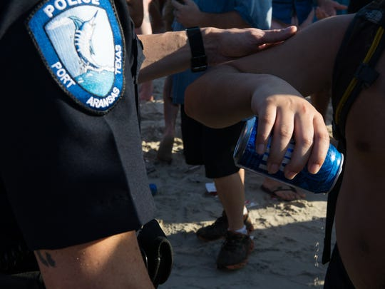 Port Aransas police officer Alan Graham has a spring breaker pour out is beer to comply with the law banning alcohol on the beach past 6pm during spring break.