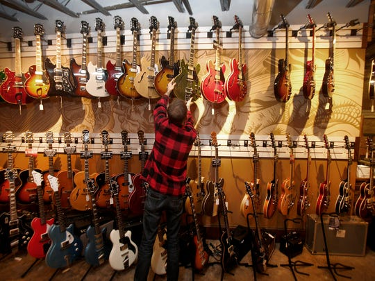 Scott Engel places an electric guitar back on the wall at Russo Music in Asbury Park Friday, March 24, 2017.