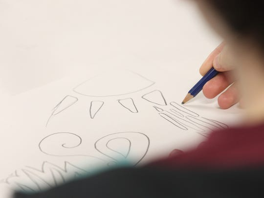 A student works on an emotion-based drawing at United