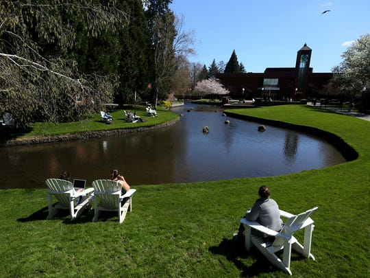 People sit in the sunshine near Mill Stream at Willamette University in Salem on Monday, April 3, 2017. Early April is bringing warmer and drier weather to the Mid-Willamette Valley.