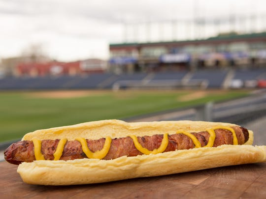 A bacon-wrapped hot dog is among the food items at Greater Nevada Field this year.