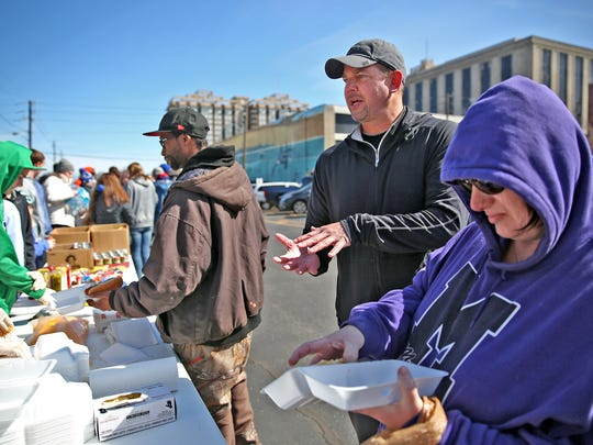 Todd Leary, center, helps out as his Indiana Faith AAU team members serve the community at the corner of St. Clair and Pennsylvania Streets last March.