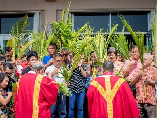 Churchgoers observe Palm Sunday at Santa Barbara Church in this April 9, 2017, file photo.