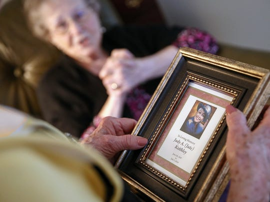 A photo of Chris Becher's biological mother Judy Keithley, who passed away in 2014, is held by Chris Becher's Adoptive mother Mary Kay Becher at her Indianapolis home, Saturday, April 1, 2017. Mary Michael, Judy's mother, is seen in the background.