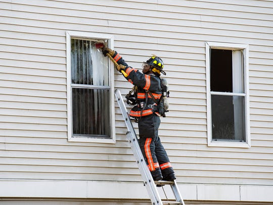 A North Collier Fire Rescue firefighter breaks a window during an apartment fire at the Bear Creek complex in Naples on Monday, April 10, 2017. The fire was reported around 2:20 p.m. on Monday at the Bear Creek Apartments off of Airport-Pulling Road.