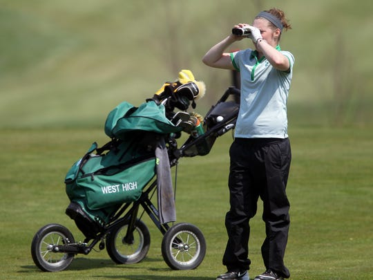 West High's Jordan Amelon checks the distance to the third hole pin at Brown Deer Golf Club on Thursday, April 13, 2017.