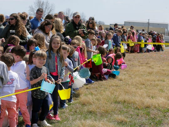 Kids wait for the start of an Easter egg hunt and the