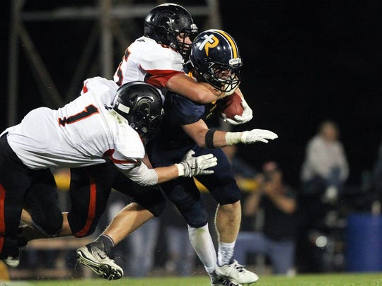 Solon's Tyler Linderbaum  (middle) tackles Regina's Isaac Vollstedt during their game at Regina on Friday, Sept. 2, 2016.
