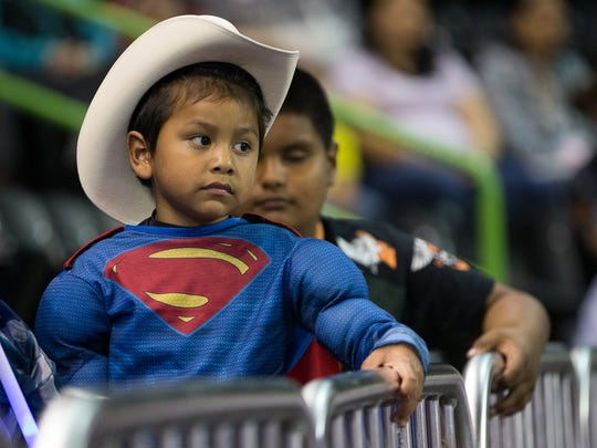 Dressed as superman with a cowboy hat on five-year-old Tiahgo Romero watches the opening night of the Rodeo Corpus Christ at the American Bank Center, Thursday, April 14, 2016.