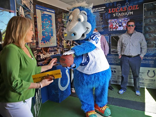 Lori Sharp, left, rubs the basketball for good luck before Indianapolis Colts mascot, Blue, goes for a long basket during fun on Monument Circle as part of Downtown Indy's Workforce Week, Monday, April 24, 2017.