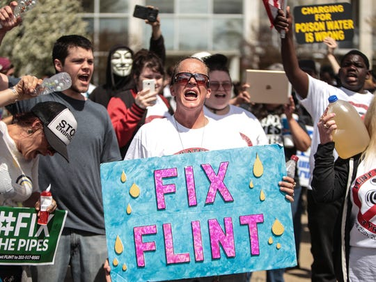 Teresa Farley (center) of Flint holds a sign while yelling with other Flint residents gathered at Flint City Hall while speaking out during the three year mark for the Flint water crisis on Tuesday April 25, 2017 in downtown Flint.
