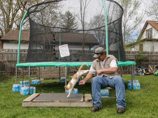 Patrick Fidler of Flint sits next to his trampoline
