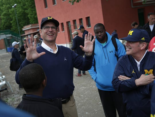 Michigan coach Jim Harbaugh talks with fans after their