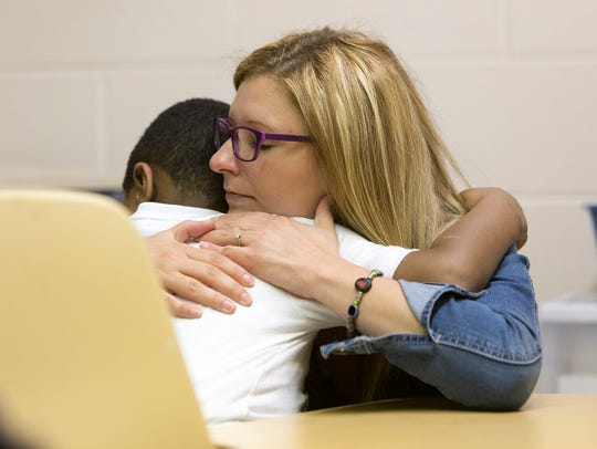 Ashley Clinton, an assistant teacher, embraces student