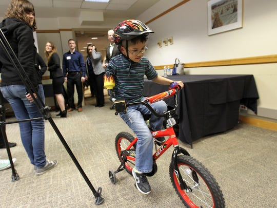 Jonny Cole rides his bicycle with a custom handlebar around the Iowa Memorial Union on Friday, April 28, 2017. Cole is an 8-year-old congenital amputee who was born missing most of his right arm. The handlebar attachment was designed by four University of Iowa students.