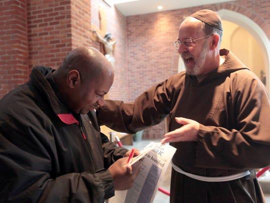 Dennis Pearson of Detroit and Fr. David Preuss celebrate