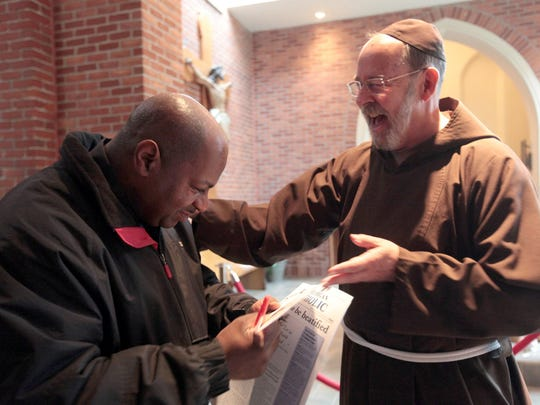 Dennis Pearson of Detroit and Fr. David Preuss celebrate
