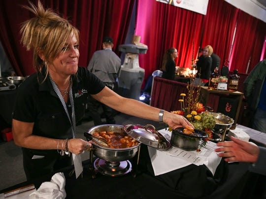 Heidi O'Hara serves food from Hops Fire Craft House during the 2017 Rev party at Indianapolis Motor Speedway, Saturday, May 6, 2017. The party, hosted by Methodist Health Foundation, raises funds for IU Health statewide trauma programs and helps kick off Indianapolis 500 festivities.
