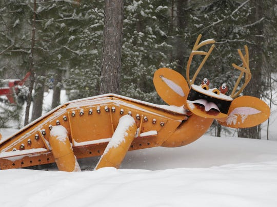 A metal creature sculpted by ironworker Tom Lakenen stretches out in the snow at his U.P. park.