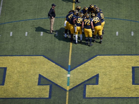Michigan football huddles with coach Jim Harbaugh watching during the team's 2017 spring game.