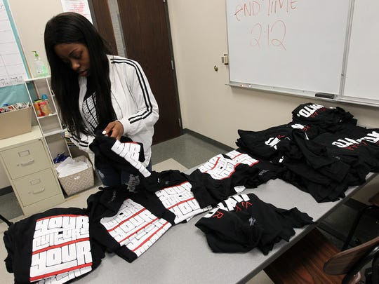 City High senior Malika Franklin sorts through shirts for her class's fashion show on Thursday, May 11, 2017.
