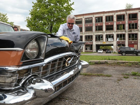 "Dave Dolby of New Baltimore wipes his 1956 Packard Executive on Tuesday, May 16, 2017 while attending the groundbreaking ceremony for the Packard Plant rehab in Detroit. Dolby brought the car to celebrate its' 61st birthday. ""She gave me a birthday getting here,"" Dolby said."