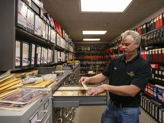 Photo retail manager Mike Roth shuffles through a cabinet of large-format film negatives. This storage room holds all the negatives from the speedway's history.