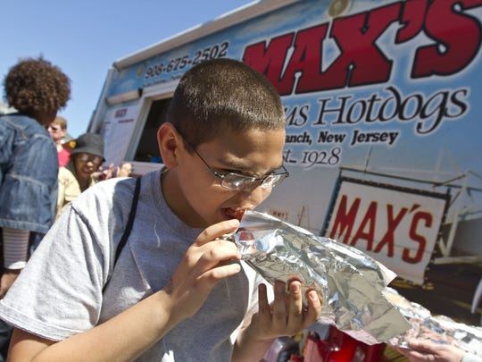 Enjoying a hot dog from Max's in Long Branch. The Jersey Shore Food Truck Festival takes place on the grounds of Monmouth Park.