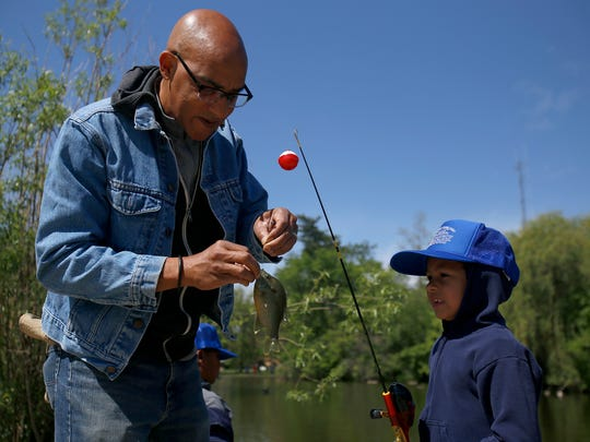 Orlando Ford, left, helps his son Renato Ford, 6, unhook a fish during the 21st annual Detroit Fishing Derby at Lake Francis in Palmer Park on Saturday, May 20, 2017 in Detroit.