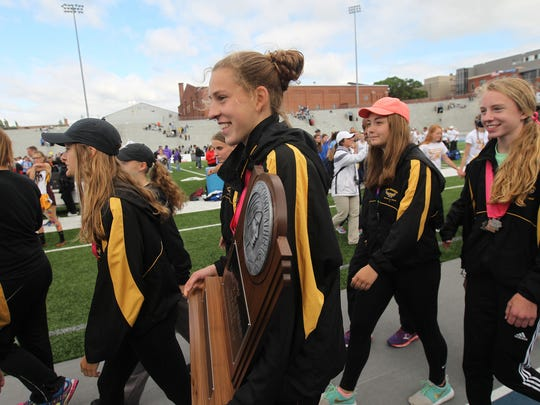 Mid-Prairie's Anna Hosteler carries her team's 2017 State Track and Field 2A runner up trophy at Drake Stadium in Des Moines on Saturday, May 20, 2017.