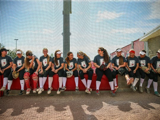 New Palestine softball players joke around during a