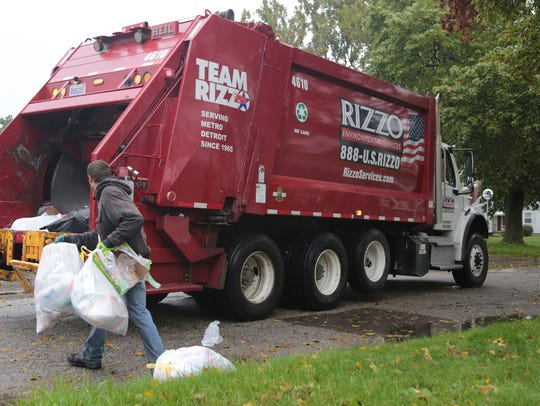 Rizzo Environmental Services workers pick up trash on Gold Avenue in Flint on Thursday, Oct. 27, 2016.