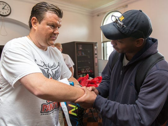 Dwight Carroll, an Army veteran, right, shakes hand