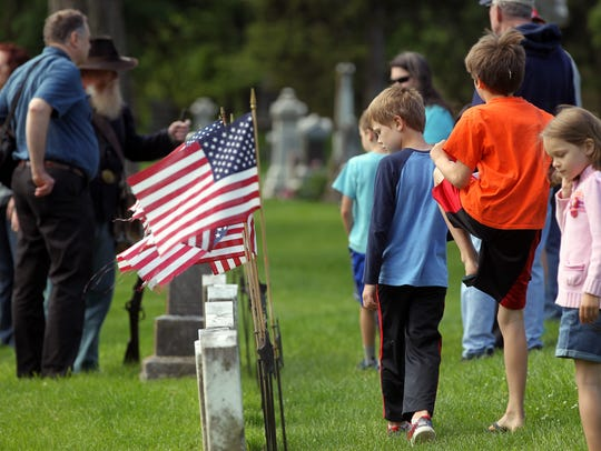 Guests attend a Memorial Day service at Oakland Cemetery