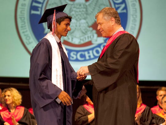 Principal Bob Schaffer, right, congratulates Arjun Gupta before he receives his diploma during Liberty Common High School's commencement ceremony in 2017.