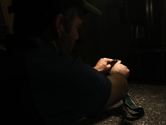 Iowa head coach Tom Brands reads an inscription on his 1996 Olympic gold medal at his home early Tuesday, May 23, 2017.