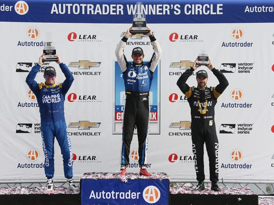 Third-place winner Scott Dixon, left, hoists his trophy with winner Graham Rahal, center, and second-place winner James Hinchcliffe, right, at the first dual of the Chevrolet Detroit Grand Prix on Saturday June 3, 2017 on Belle Isle.