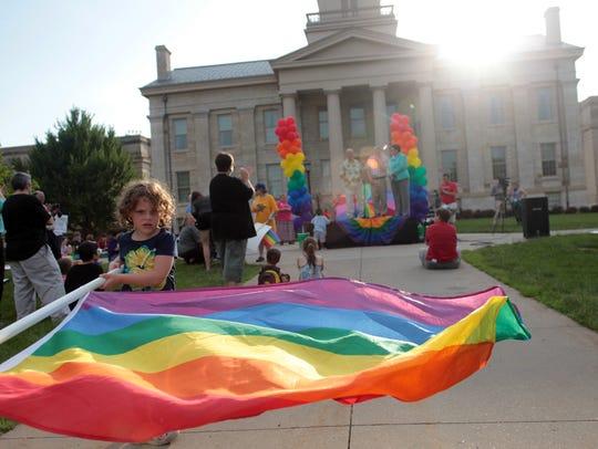 Christian Julian, 4, of iowa City waves a pride flag