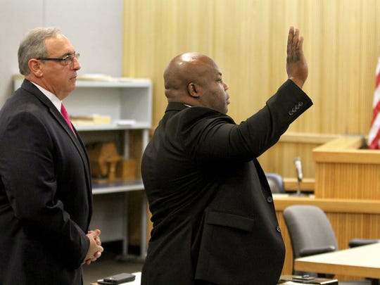 Former Asbury Park police officer Alix Antoine, 38, of Neptune is sworn in before his PTI hearing for insurance fraud before Judge Leslie-Ann Justus in Freehold Friday, June 9, 2017.   At left is Antoine's attorney Richard Incremona.