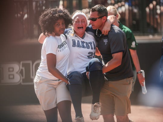 Macomb Dakota pitcher Kendahl Dunford is carried out the field after getting injured during the Division 1 softball state title game against Farmington Hills Mercy on June 18, 2016, in East Lansing.