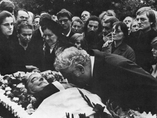 A scene from Dmitri Shostakovich's 1975 funeral in Moscow's Novodevichy Cemetery. Composer Aram Khachaturian is seen kissing the composer's hand.