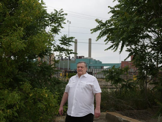 David Lanciault stands on land he owns across from