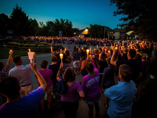 Hundreds of mourners raise candles to the sky at dusk last June during a vigil for Amanda Strous at her family home in York Township. A year later, there are two scholarships and a foundation in Amanda's name