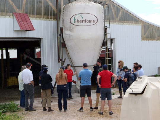 Ashley Schlender (center) talks to 11 farmers from around the world during a tour of Nuffield Scholars at their Jefferson County farm, Never Rest Dairy, on June 19. It's the first time the tour stopped in Wisconsin during its U.S. tour.