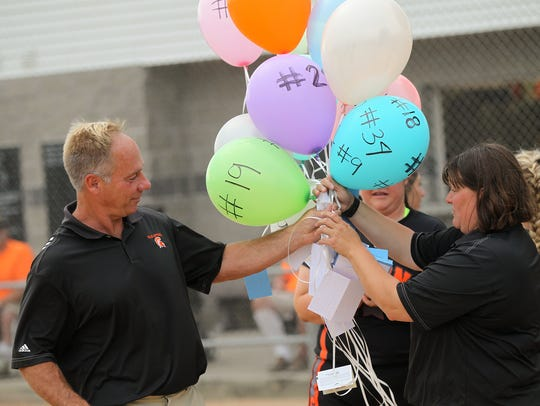 Solon head coach Jim White receives balloons from players