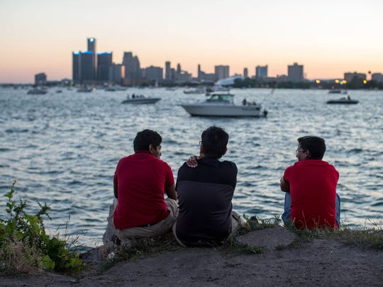People sit along the banks of the Detroit River and