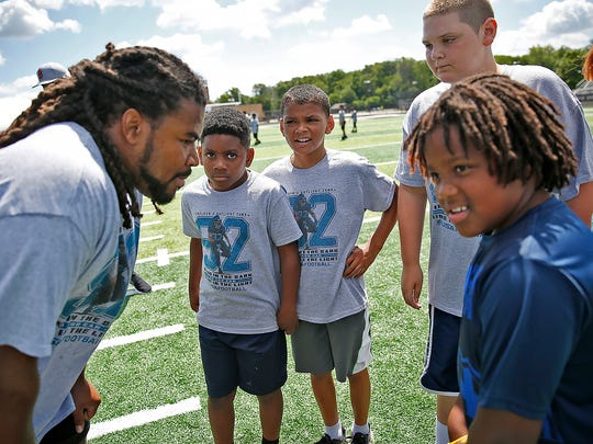 Former Warren Central High School and Notre Dame football star Sheldon Day, left, huddles with the kids before a play at the Sheldon Day Camp at Warren Central High School, Saturday, June 24, 2017.